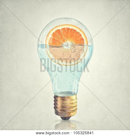 Glass lightbulb filled with water and half of orange fruit