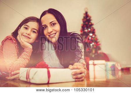 Festive mother and daughter smiling at camera at home in the living room