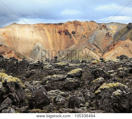 National Park Landmannalaugar in Iceland. Pieces of gray and black lava, sometimes covered with green moss. In the background - blue and orange rhyolite mountains