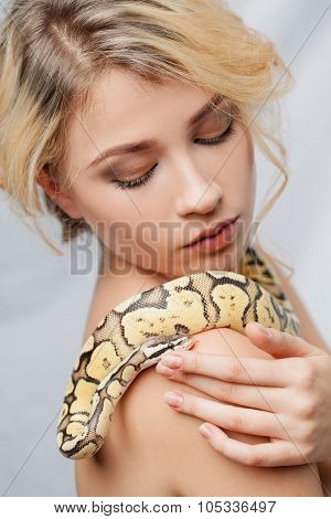 Beautiful girl  holding a python, which wraps around her body