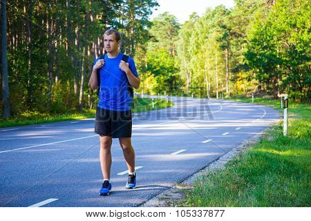 Hitchhiking Concept - Man Hiker With Backpack Walking On Forest Road