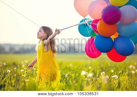 Smiling girl with balloons in the field