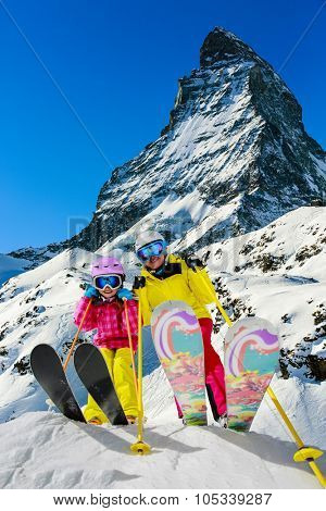 Ski, winter, snow - skiers enjoying winter vacation in Swiss Alps, mountain view Matterhorn