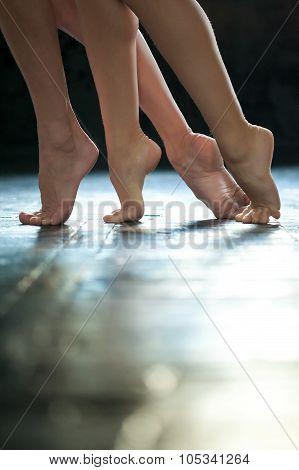 Close-up Ballerina's Legs On The Wooden Floor
