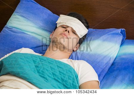 Young sick or unwell man in bed