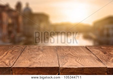 Empty wooden table against sunrise in Venice on background