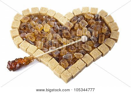 Heart from not refined reed sugar and candy sugar on a stick
