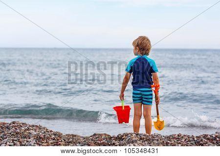 Kid Boy Standing On Lonely Ocean Beach