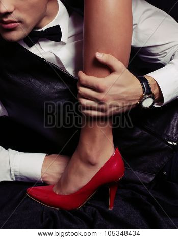 women power.woman's leg in red shoes beside handsome man wearing business suit