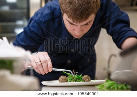 Closeup of concentrated male chef garnishing food in kitchen