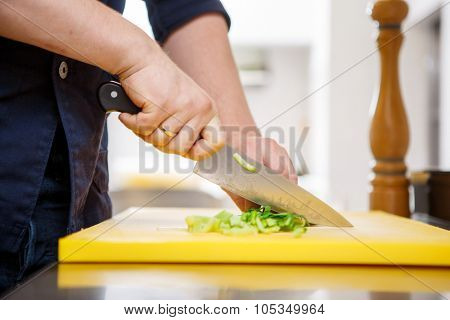 Chef chopping greens over yellow carving board