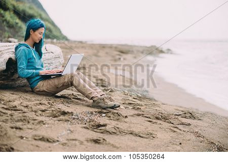 Freelancer girl with laptop on beach