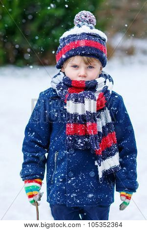 Sad Kid Boy In Colorful Winter Clothes Having Fun With Snow, Outdoors