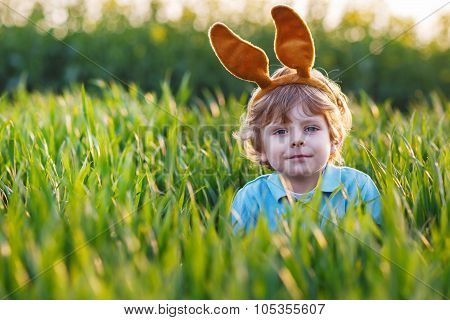 Cute Blond Kid Boy With Easter Bunny Ears Playing In Green Fieldon Sunny Spring Day, Celebrating Eas
