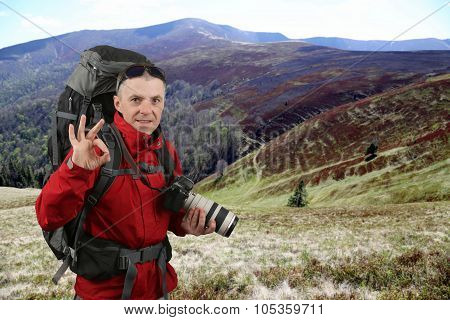 Photographer Traveler In The Red Jacket On The Elephant Mountain Is Showing Hand Ok Sign
