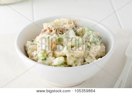 homemade potato salad made with red potatoes, celery sticks, red onions and fresh herbs in white bow
