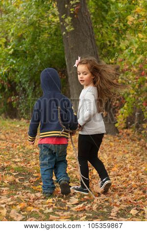 two young children walking in a park dragging together a long stick