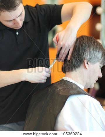 A man cuts hair in a barbershop. Master young stylist.