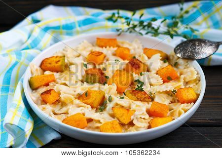 Pasta with pumpkin and thyme with creamy cheese sauce. Farfalle