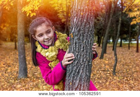 Cute Little Girl Smiling By The Tree