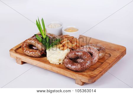 sausages with mashed potatoes, wooden board, isolated, white background, fried green onions, parsley