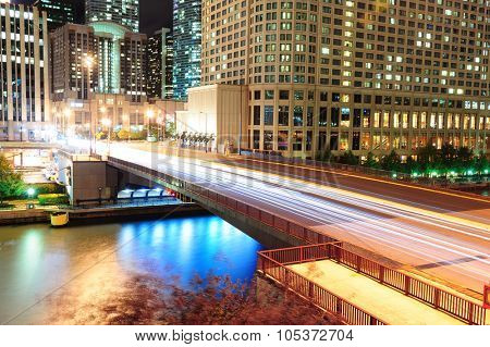 Bridge over Chicago River with urban skyscrapers illuminated with lights and water reflection at night.