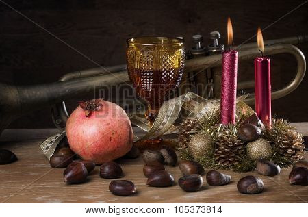 Rustic traditional christmas still-life with wine, seasonal fruits and a old trumpet
