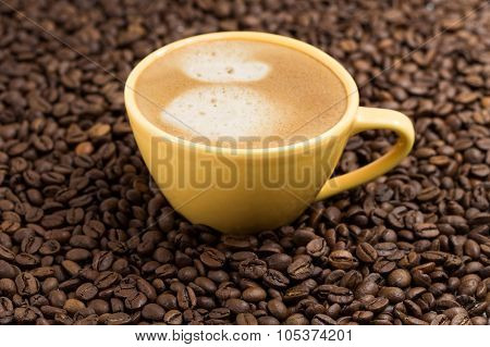 Yellow Coffee Cup And Roasted Coffee Beans Around