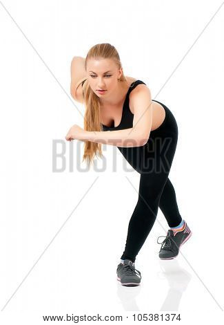 Young sportswoman doing stretching exorcises on a white background