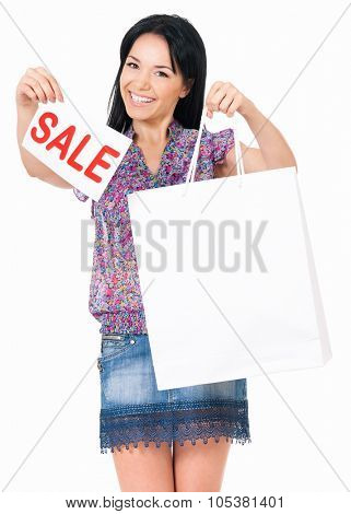 Portrait of young happy smiling woman with shopping bags showing signboard announcing a Sale, isolated over white background
