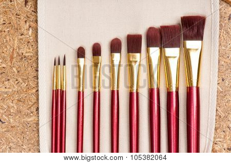 Professional makeup brushes on wood background - top view