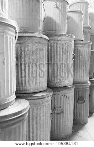 Old galvanized steel metal trashcans in black and white.