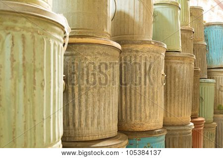 Landscape image of old metal trash cans with lids
