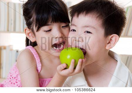 Asian kids eating apple