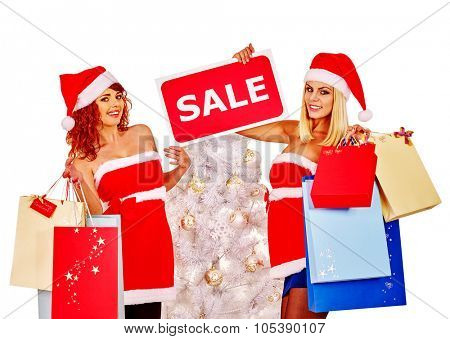 Women in red short dress and Santa hat holding sign saying sale with gift box.
