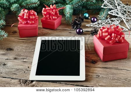 White Tablet Computer With Christmas Gifts On Wooden Table Closeup