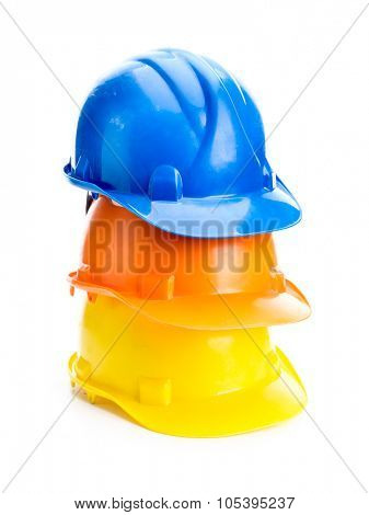 Three hard hats in blue, orange and yellow colors piled up shot on white background