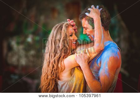 happy young pair in paints holi