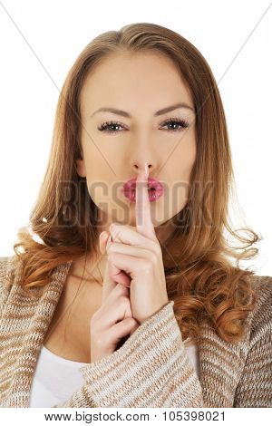 Serious woman placing finger on lips.