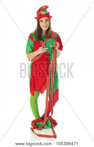 A pretty teen elf looking at the viewer while holding a large spool red and green ribbon.  Some of it is wrapped over and around her.  On a white background.