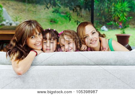 Two proud hispanic mothers posing with their daughters, heads sticking up from sofa and smiling to c