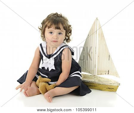 A beautiful barefoot baby looking at the viewer in her sailor dress, a toy sail boat behind her.  On a white background.