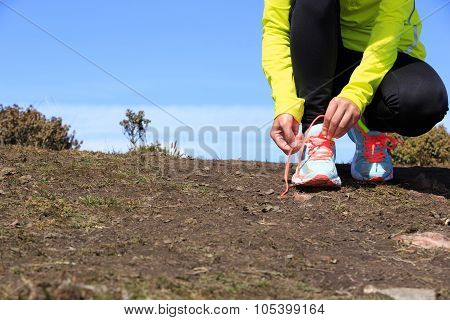 Young Woman Trail Runner Tying Shoelace On Mountain Peak