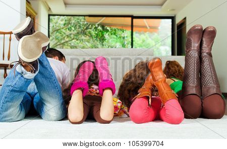 Family of four lying down facing away from camera with feet up in air