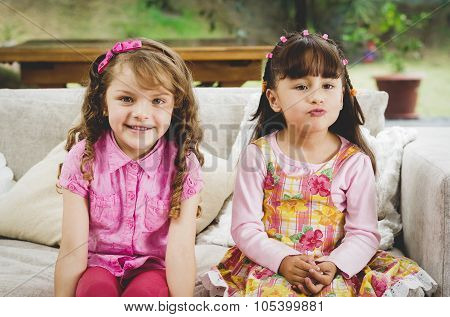 Brunette children sisters sitting happily on white livingroom sofa posing for camera with typical pi