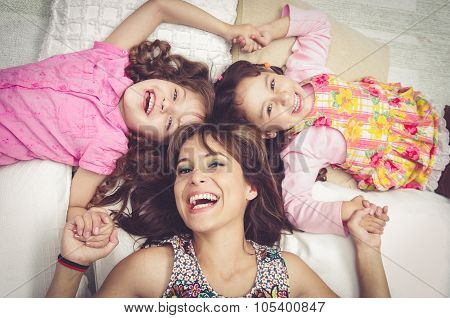 Young adorable hispanic sisters and mother lying down with heads touching, bodies spread out differe