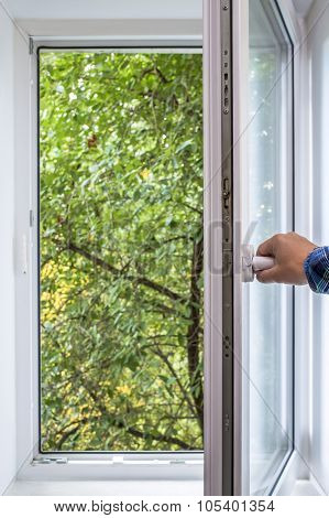 man opens pvc window