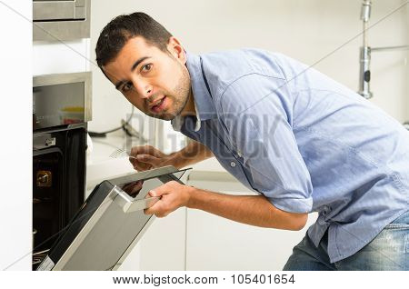 Hispanic male wearing blue shirt in modern kitchen leaning towards open oven door holding a fork loo