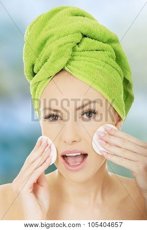 Shocked caucasian woman with cotton pads.