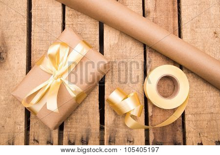 Nicely wrapped presents in brown and golden wrapping on wooden surface